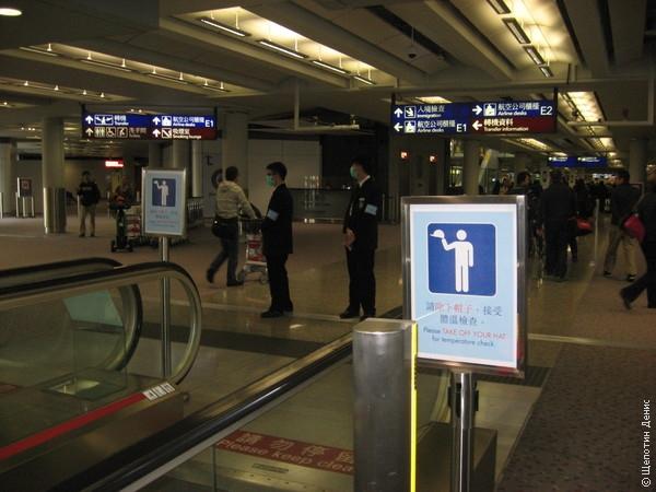 """Плакат \""""Снимите шляпу для измерения температуры\"""" в аэропорту Гонконга как напоминание о боях с \""""птичьим\"""" и прочими гриппами"""